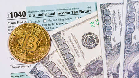 Bitcoin on Tax day. 1040 form ready to be filled and returned. Reklamní fotografie