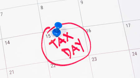 Pinning tax day on April 15 calendar and marked in red. Deadline for 1040 form return.