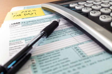 Tax day. 1040 form and calculator on table ready to be filled and returned.