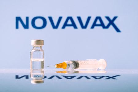 Novavax Coronavirus Vaccine vial and syringe with logo as background. LJUBLJANA, SLOVENIA: March 25, 2021