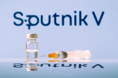 Sputnik V Coronavirus Vaccine vial and syringe with logo as background. LJUBLJANA, SLOVENIA: March 25, 2021