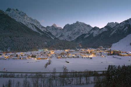 Kranjska gora at winter with lights at twilight in Slovenia. Alpine ski resort tourism. Reklamní fotografie