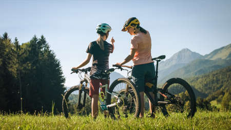 Two females on mountain bikes talking and looking at beautiful green nature. 版權商用圖片