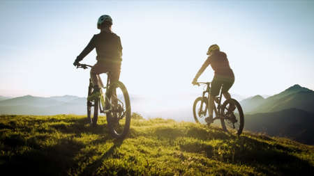 Tweo females on mountain bikes riding and looking at sunset