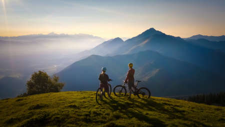 Two females on mountain bikes talking and looking at beautiful sunset 版權商用圖片