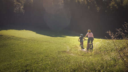 Woman and girl child riding mountain bikes on a country road in nature on a bright sunny summer day.
