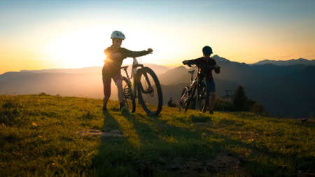 Mother and daughter walking uphill with mountain bike at a sunset.