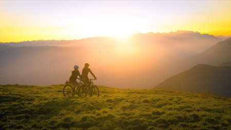 Mother and daughter cycling uphill with mountain bikes at a sunset. 版權商用圖片