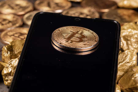 Bitcoin cryptocurrency on smartphone with gold nuggets. Investment and store of value concept.