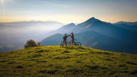 Two happy woman high five over the sunset after a successful mountain biking trip in the mountains. Celebrate a cross country cycling journey.