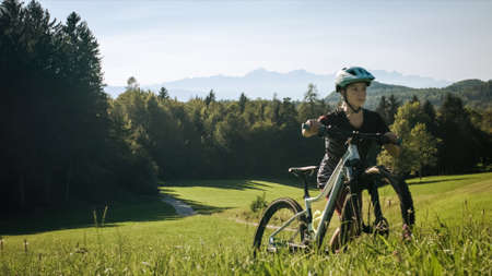 Girl child walking uphill with mountain bike in nature on a beautiful day.