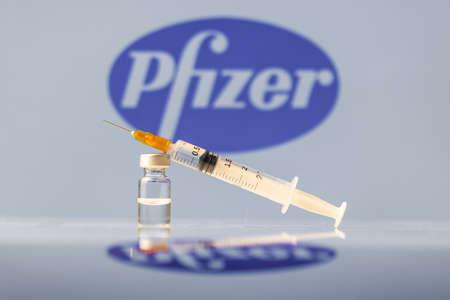 Pfizer Coronavirus Vaccine vial and syringe with logo as background. LJUBLJANA, SLOVENIA: March 25, 2021