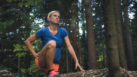 Close up of a Caucasian woman doing hip flexor stretch in the forest, raising her foot on a reclining tree 版權商用圖片