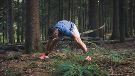 Wide shot of Caucasian man in sportswear doing legs and back stretching exercises in the forest 版權商用圖片