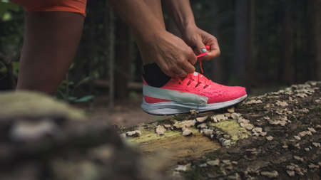 Close up of a Caucasian female foot in the running shoes, hands tying laces