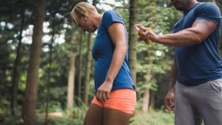 Caucasian couple in sportswear standing in the forest. Man applying spray-on womans hands and back while she drives away ticks and mosquitoes