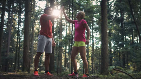 Smiling Caucasian couple in sportswear standing in the forest, giving high five to each other
