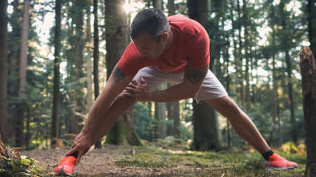 Caucasian athletic man doing cool-down stretching exercises in the forest, after running