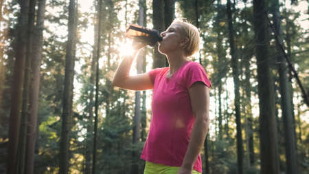 Middle shot of a Caucasian woman in sportswear standing in the forest, drinking water from a bottle 版權商用圖片