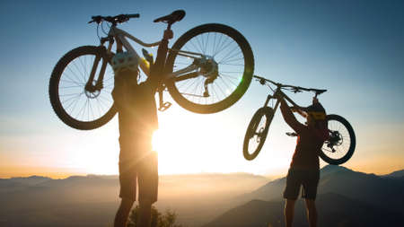 Two cheerful woman lifts his bicycle above his head at sunset after a winning mountain biking ride.
