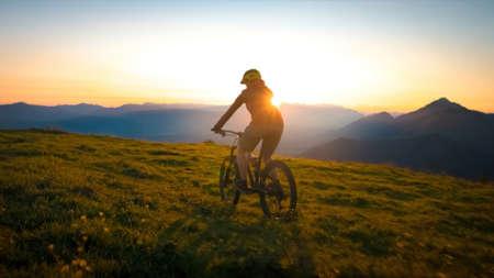 Woman riding mountain bike into the sunset. Beautiful golden summer light.