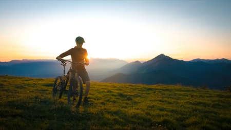 Woman walking uphill with mountain bike at a sunset. 版權商用圖片