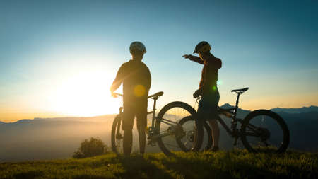 Two silhouettes standing near mountain bikes, talking and observing view in the background, mountaintops