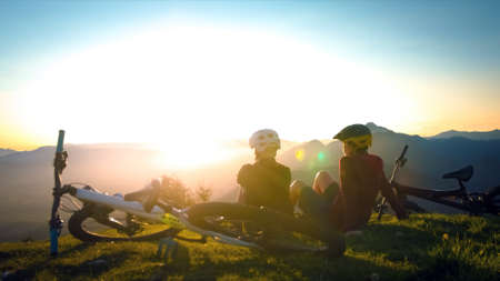 Girls sitting on mountain with bycicles looking at sunset and talking. Enjoying in beautiful nature.