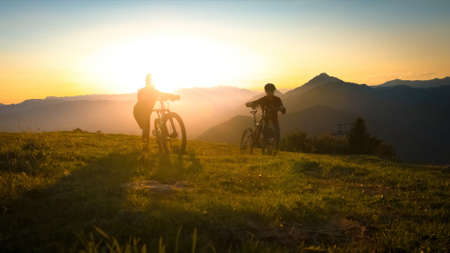 Two silhouettes pushing a mountain bike, across the meadow at the top of the hill during sunset