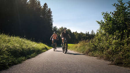 Mother and daughter riding mountain bikes in the country road in green nature on a sunny day. 版權商用圖片