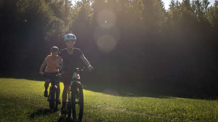 Two girls on mtb bikes. Mother and daughter riding on a forest trail.