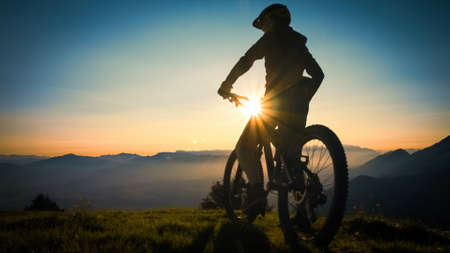 Wide shot, back view of silhouette sitting on a mountain bike, enjoying an amazing view