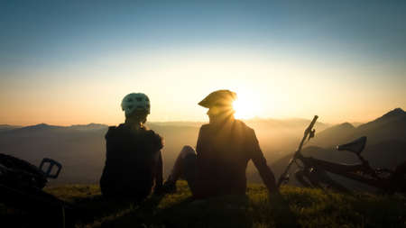 Two female cyclists sitting on the grass, talking and looking at mountains in the distance at the sunset