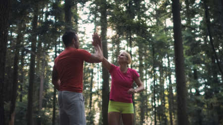 Smiling Caucasian couple running in the forest, at the end of the run giving high five to each other