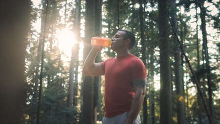 Middle shot of a Caucasian man in sportswear standing in the forest, drinking water from a bottle 版權商用圖片