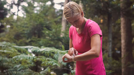 Middle shot of a Caucasian woman adjusting a smartwatch before running