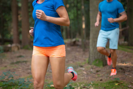 Caucasian couple in sportswear running in the forest, between trees