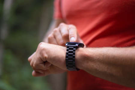 Close up of male hands, right-hand forefinger setting a data on a smartwatch