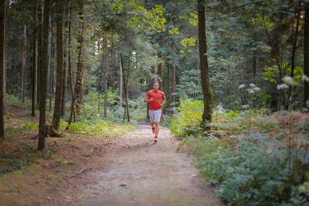 Caucasian man in sportswear running along a forest trail