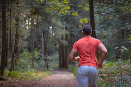 Back view of a Caucasian man in sportswear running along a forest trail, close up