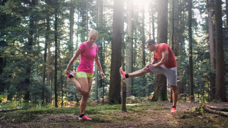 Caucasian woman and man in sportswear doing post run leg stretching exercises in the forest