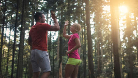 Caucasian couple running in the forest, at the end of the run giving high five to each other 版權商用圖片