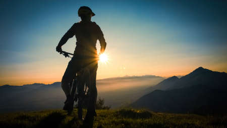 Silhouette of a woman on mountain bike looking at sunset