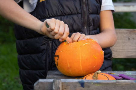 Boy carving pumpkins for halloween in the backyard. Fun family activity.