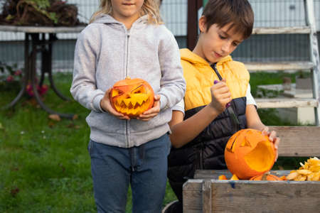 Boy and a girl carving pumpkins for halloween in the backyard. Fun family activity.
