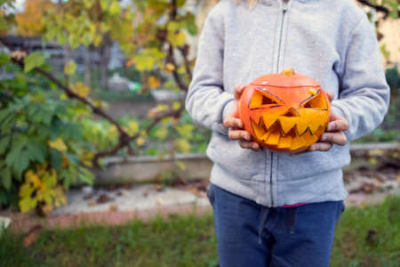 Child holding carved pumpkin for halloween in the backyard. Fun family activity.