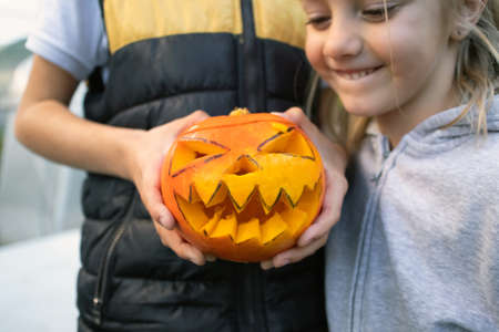 Child holding and open top of a carved pumpkin with ghoulish face, jack-o-lantern, in the background boy sitting at the table and decorating pumpkin