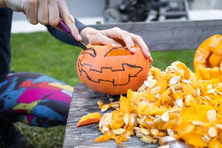 Carving pumpkins for halloween in the backyard. Fun family activity. 版權商用圖片