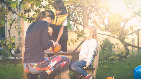 Family preparing decorations for Halloween in the yard, slicing the top of a pumpkin and hollowing it out