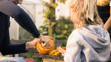 Handheld shot of a caucasian family, mother hollowing out and scraping down the inside pumpkin, son and daughter watching her